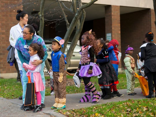 Charlene Santos, who works in the kindergarten/first grade program at the Greater Ithaca Activities Center talks with five-year-old Janelle Lucena as they wait to lead the annual parade from McGraw House to The Commons for trick or treating Friday.