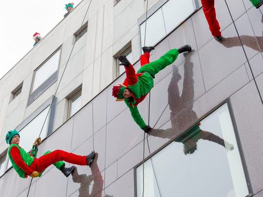 Santa's elves, who are Lt. Jake Young, left and Sgt Bob Brotherton, with the Ithaca Police Department SWAT team descend the Center Ithaca building Saturday on The Commons, in advance of Santa.