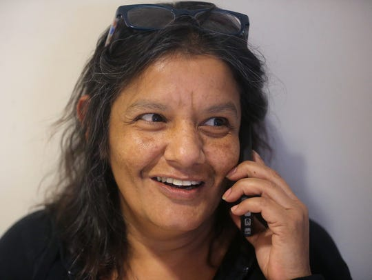 Judith Brown, uses a cellphone to contact a family