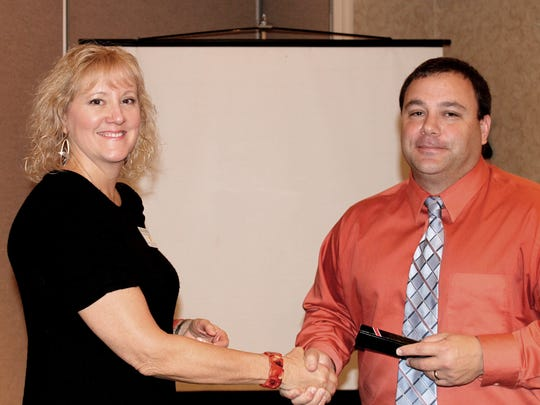 York East Rotary President Linda Gorter, left, shakes hands with Tony Forella, juvenile probation supervisor.