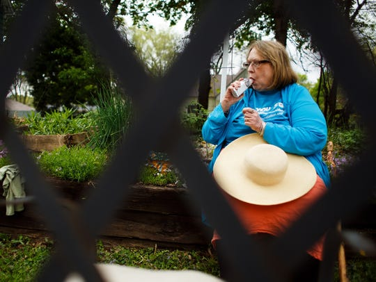 Kathy Stangl uses a nebulizer as she gardens home on