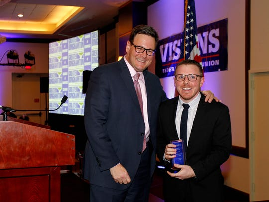 Jon Sarra, left, presents the Small Business Person of the Year Award to Ben Giordano, of FreshySites.