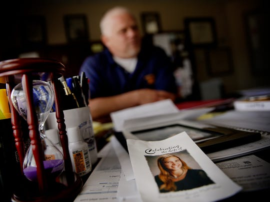 The funeral program for Leah Cooper McMillan sits on the desk of Johnson County Prosecutor Brad Cooper, McMillan's older brother,  June 7, 2016. McMillan died of a heroin overdose at 26.