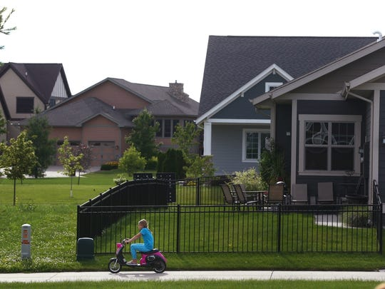 Emerson Manus, 8, rides a scooter around the green space in the middle of the cul-de-sac where her family lives in the Prairie Trail subdivision in Ankeny on Thursday, June 18, 2015. The cul-de-sac has a public green space for all the homes to use as the size of homes continues to grow and lot sizes continue to shrink.