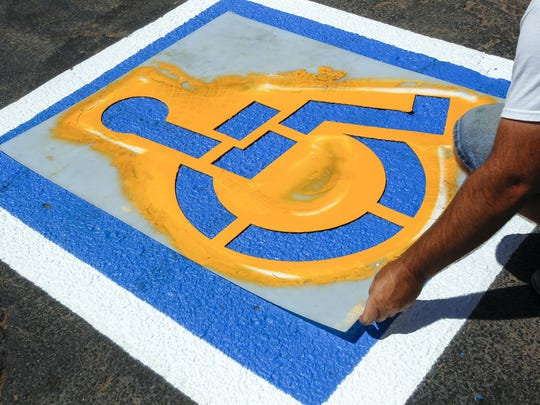Jeff Tetzloff, of Maricopa, lays a stencil out on the new disabled parking stall at Y-Knot Party & Rentals in Mesa on July 14, 2016. The business is restriping the handicap stalls in their parking lot to meet accessibility requirements outlined by the Americans with Disabilities Act.