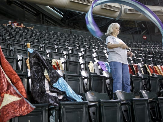 """Cindy McBride, known as """"the flag lady"""" at Arizona Diamondbacks games, waves a flag for the Diamondbacks during their home-stand game against the Los Angeles Dodgers on July 17, 2016. She usually sits in the upper-deck where she can lay her flags out across the seats. She has one for each player in the starting lineup."""