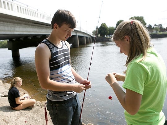 Courtney Steinkamp fishes as her sister Haley puts bait on a fishing pole for Nick Keuntjes