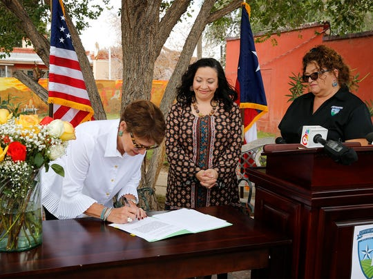 Mauren Ponce Singleton, signs over 150-acres of land to San Elizario Mayor Maya Sanchez as City Clerk Nancy Montes looks on. In a small ceremony held on grounds of Surratt Farms, Mayor Sanchez presented the key to the City of San Elizario to Singleton, along with a proclamation shortly before Singleton signed over the land to the City of San Elizario. The land which at one time was home to Surratt Farms until the early 2000's is now known as Valley Feed Mills.