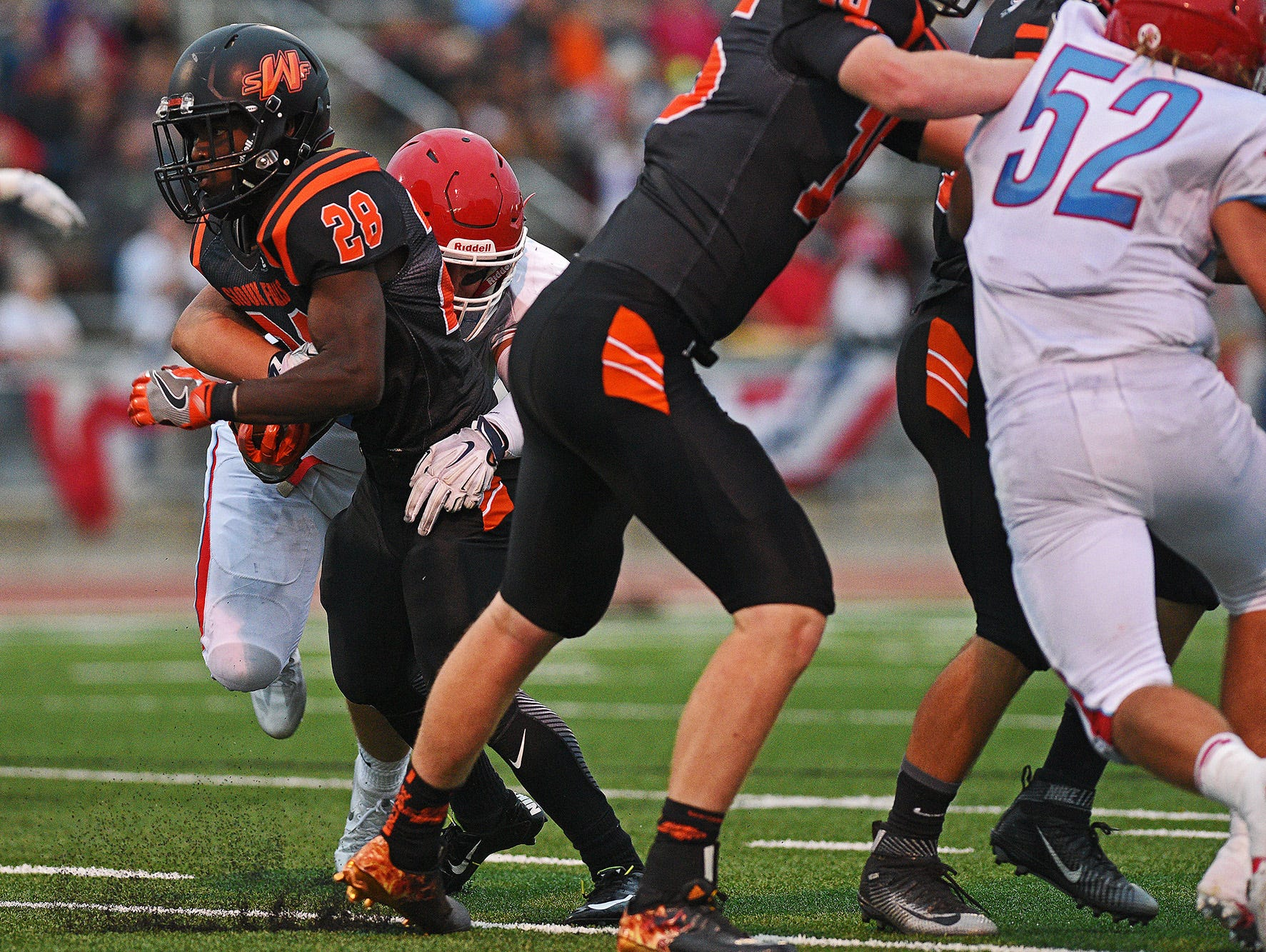 Washington's Tupac Kpeayeh (28) is brought down by Lincoln's Xavier Kolb (44) during a Presidents Bowl game at Howard Wood Field Saturday, Sept. 3, 2016, in Sioux Falls.