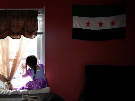 Zouabi's daughter Maram, 6, looks out the window to
