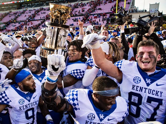 The UK football team celebrates after beating Louisville at Papa John's Cardinal Stadium in the Governor's Cup 41-38. Nov. 26, 2016