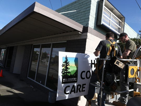 Wright Electric owner Jeremy Wright, left, and helper Jake Ratliff install a sign Wednesday at Hill Country Health & Wellness Center in Redding. The facility is opening on March 12.