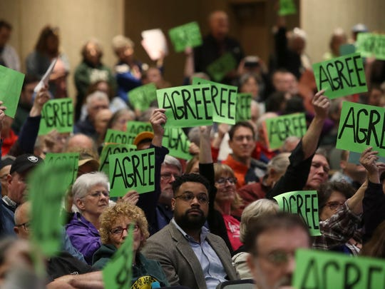 Audience members hold up cards during a question at