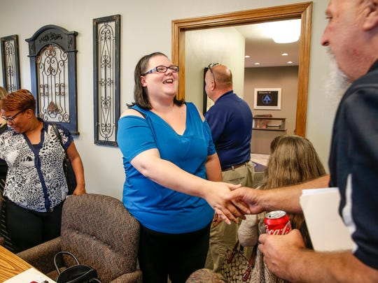 "Laura Warrick shakes hands with the seller's realtor after signing a stack of papers during the closing of her first home at Abstract & Title in Avon, Ind., on Friday, August 4, 2017. Warrick worked with Hawthorne Community Center for four years to erase $10,000 in debt and save up for the home. ""I'm excited for my son to have his forever home,"" she said."