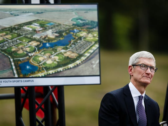 Apple CEO Tim Cook sits in front of a rendering of