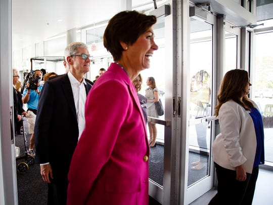 Apple CEO Tim Cook, left, and Gov. Kim Reynolds visit