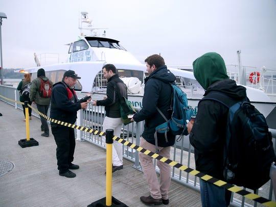Deck hand Art Espitia scans  passenger tickets as commuters