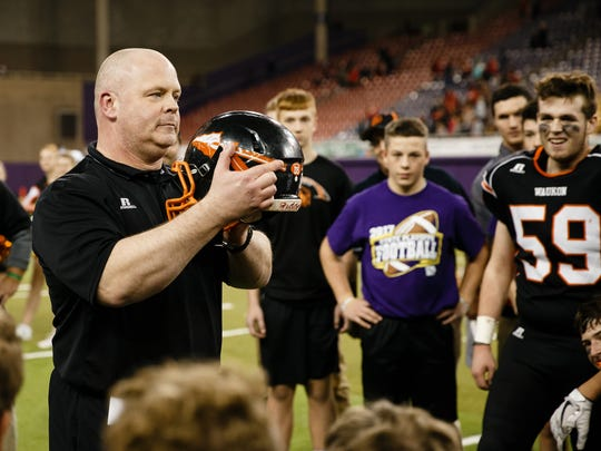 Waukon head coach Chad Beerman points to a sticker in honor of David Schoeberlein who was a teacher and coach at Waukon that passed away in September. Waukon defeated Williamsburg 29-0 in the class 2A state final football game at the UNI Dome on Friday, Nov. 17, 2017, in Cedar Falls.