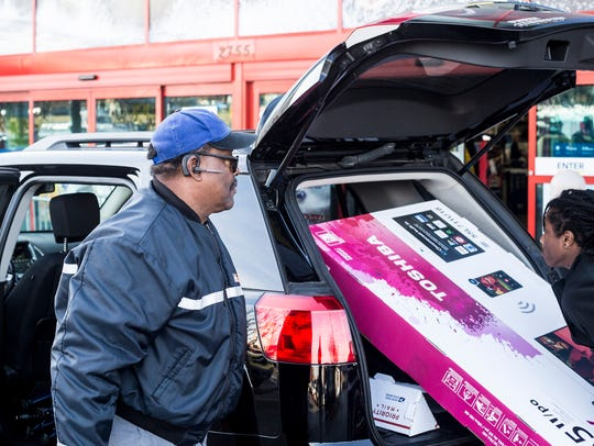 Michael Micklin, of Cordova, watches as a brand new big screen television is loaded into his SUV on Black Friday in 2017.