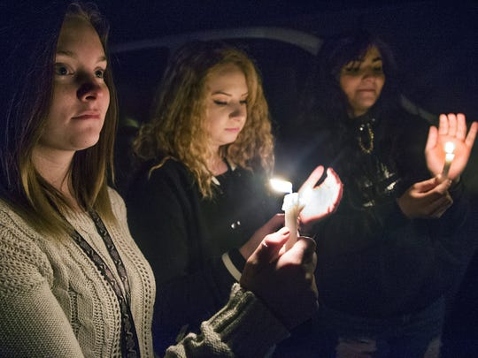 Dallas Baron, 18, left, Nevaeh Jaramillo, 15, and Heaven Hughes, 15, hold candles during a Thursday night vigil for the Aztec High School shooting victims in Minium Park in Aztec.