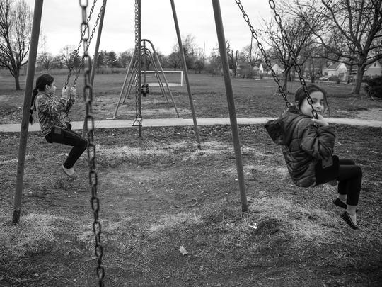 Valeria Ordac, 9, and sister Adriana, 7, swing in Near West on Thursday, March 23, 2017. With rainy weather coming the two wanted to get outside and play.