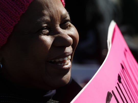 Linda Masuku, 59, originally from South Africa and now residing in Grinnell holds a sign in front of the Iowa State Capitol during the Iowa Women's March on Saturday, Jan. 20, 2018, in Des Moines.