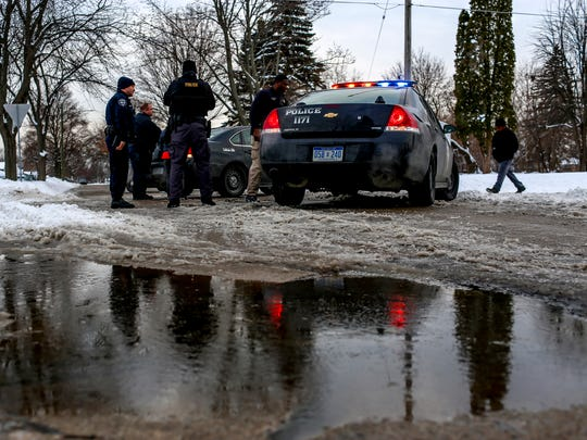 Saginaw Police officers talk amongst themselves while investigating a scene where a boy allegedly shot a pellet gun at a bus carrying home children from school at the intersection of 22nd Street and Cherry Street.