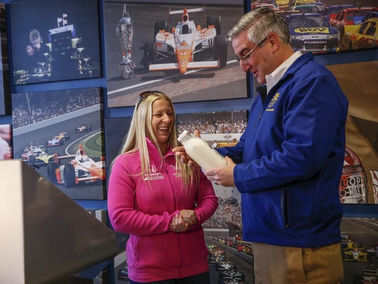 Indiana Gov. Eric Holcomb accepts an official Indy 500 101st Running milk bottle from IndyCar driver Pippa Mann before officially installing the checkered flag atop the Indianapolis Motor Speedway Gate 1 on Friday, March 10, 2017. The annual ceremony marks the start of the 2017 Verizon IndyCar Series season and the countdown to the 101st Indianapolis 500 presented by PennGrade Motor Oil.