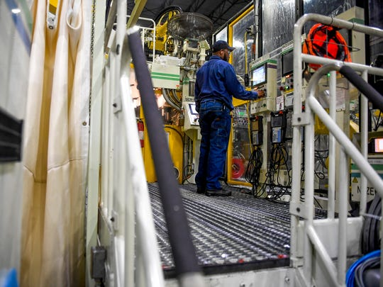 Jamal Daniels stands at his station operating machinery at the Toyota Bodine plant in Jackson, Tennessee on Thursday, July 5, 2018.