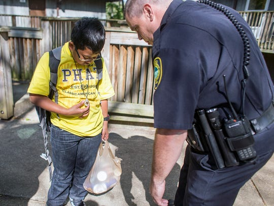 """Officer Albert Ball, right, talks with Klondyke Homes resident Ed Alvarado, 12, during an Asheville Police Department walk-through last week. Alvarado said he thinks the officers walking through is scary, but great. """"It's just kind of weird and kind of scary, but it's like a happy feeling, too."""""""