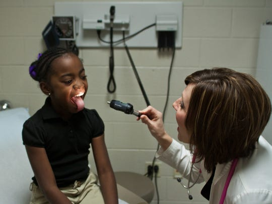 Mandy Braswell, pediatric nurse practitioner at the West Tennessee Healthcare School Health Clinic, gives a check-up to A'deysiah Galloway, a second-grader at Jackson Careers and Technology Elementary School.
