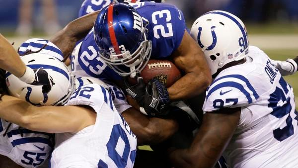 Giants running back Rashad Jennings (23) is stacked up by Colts defender during the first half of Saturday night in Indianapolis. The Giants were shut out for the first three quarters.