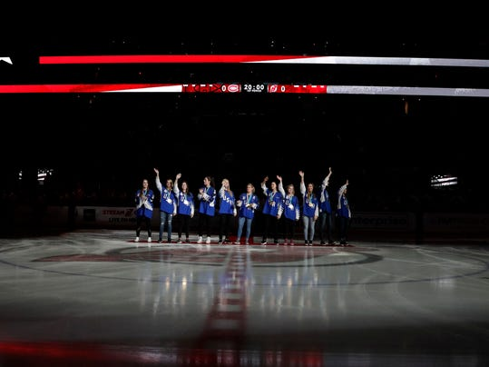 Members of the United States women's ice hockey PyeongChang Olympics gold medal team stand at center ice prior to the ceremonial puck drop with New Jersey Devils defenseman Andy Greene (6) and Montreal Canadiens right wing Brendan Gallagher (11) prior to an NHL hockey game, Tuesday, March 6, 2018, in Newark, N.J. (AP Photo/Julio Cortez)