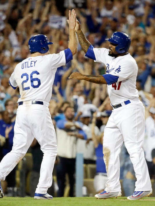 Los Angeles Dodgers' Chase Utley, left, and Howie Kendrick celebrates after scoring on a hit by Adrian Gonzalez during the seventh inning in Game 2 of baseball's National League Division Series against the New York Mets, Saturday, Oct. 10, 2015 in Los Angeles. (AP Photo/Gregory Bull)