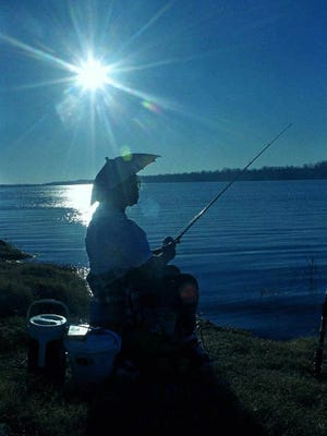 """This is a file photo of a woman fishingalong the shores of Lake Ferguson in Greenville, Miss. """""""
