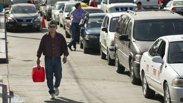 Sergio Mejia of Mexicali, Mexico walks with an empty canister to get gas while others wait in line with their vehicles to get gas near a Pemex gas station in San Luis, Sonora, Mexico on Tuesday, January 10, 2016. Gas shortages from protestors blocking supply routes from the gas distribution center in nearby Mexicali, Mexico, left only a few gas stations open in the region. The people blocking the supply routes were protesting gas prices in Mexico.
