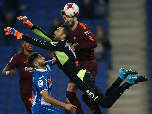 FC Barcelona's Gerard Pique, right, heads for the ball next to Espanyol's goalkeeper Diego Lopez during the Spanish Copa del Rey, quarter final, first leg, soccer match between Espanyol and FC Barcelona at RCDE stadium in Cornella Llobregat, Spain, Wednesday, Jan. 17, 2018. (AP Photo/Manu Fernandez)