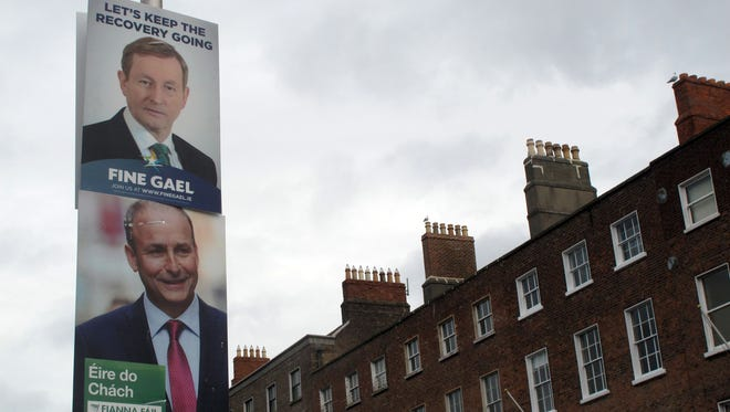 Rival election posters for Fine Gael leader Enda Kenny and Fianna Fail leader Micheal Martin adorn a lamp post in Dublin on  Feb. 5, 2016.