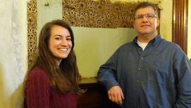 Emily Rebmann and Chris Buchanan, of the Ohio History Connection, look for clues to shed light on what the Harding Home looked like in 1920. Behind an overmantel, they recently found two layers of wallpaper, with the light blue one possibly being the wallpaper that was there in 1920.