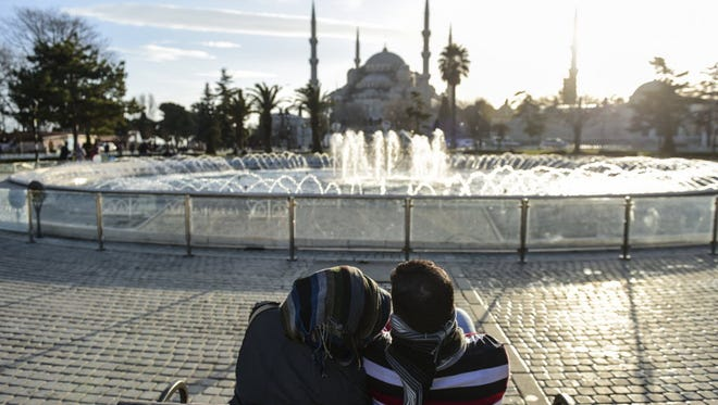 People sit outside the Blue Mosque near the site of a blast in Istanbul's tourist hub of Sultanahmet on Jan. 12, 2016.
