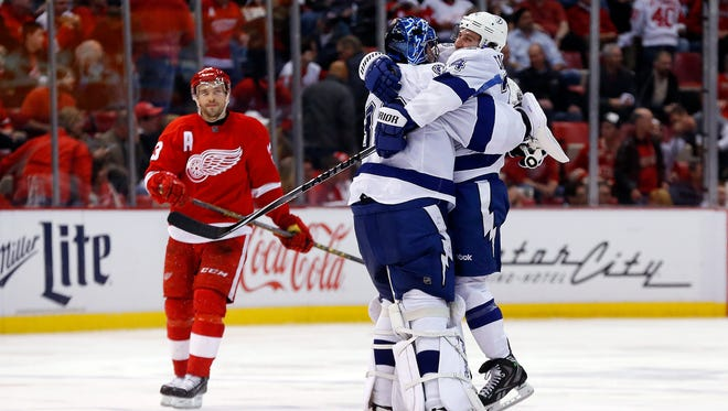 Tampa Bay Lightning goalie Ben Bishop, middle, celebrates with Ryan Callahan as Detroit Red Wings center Pavel Datsyuk, left, skates off the ice after a Tyler Johnson goal in overtime of Game 4 on Thursday, April 23, 2015, in Detroit.