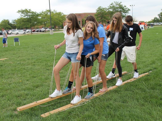 Freshman work together to move their wooden skis, a