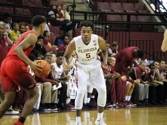 Florida State guard P.J. Savoy plays defense against