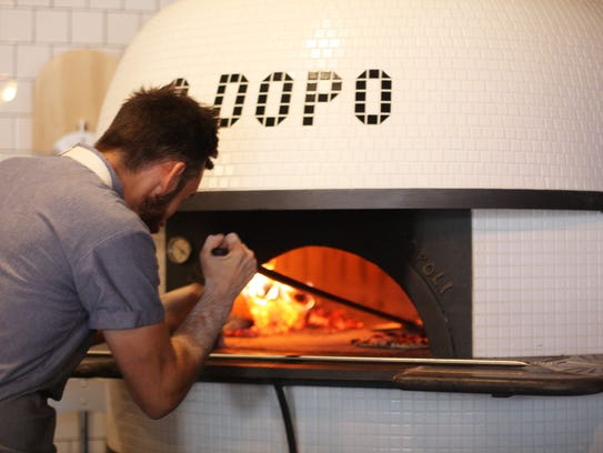 A Dopo's wood-fired sourdough pizzas are served on 13-inch white porcelain plates made in Italy.