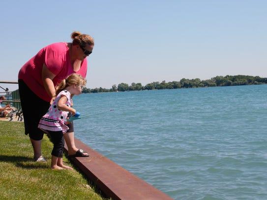 Joy Yax and her daughter, Deziray Yax, 3, fish on the