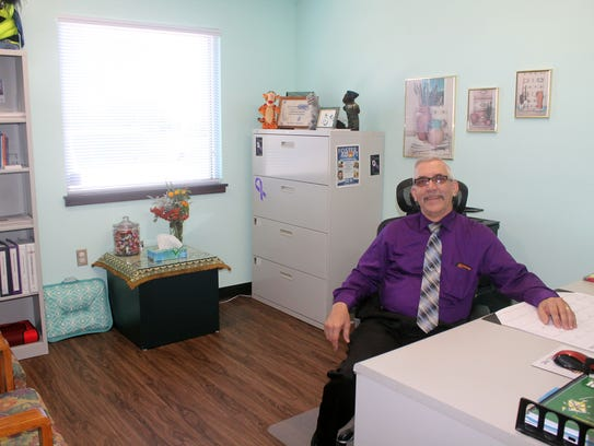 Perry Lawson, Community Educator and Domestic Violence Specialist sits in his newly renovated office space during COPE's open house Thursday.