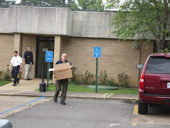 A federal agent carries a box out of the Ball Municipal