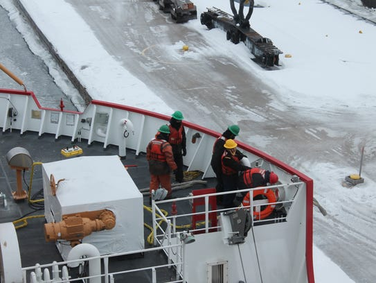The crew of Coast Guard Cutter Mackinaw work lines