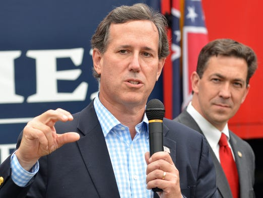 Senator Rick Santorum of Pennsylvania speaks as Republican senatorial candidate Chris McDaniel listens during a political rally Thursday by the red caboose on Main Street in Madison.