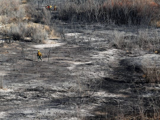 Members of the Bureau of Indian Affairs Wildland Fire Management from Fort Defiance, Ariz. work on Monday, Dec. 4, 2017. Crews continue to work the scene of a brush fire that occurred on Sunday evening in Shiprock.